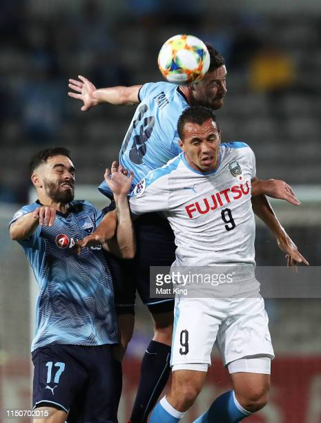 Leandro Damião of Kawasaki Frontale is challenged by Anthony Caceres and Jacob Tratt of Sydney FC during the AFC Asian Champions League match between...