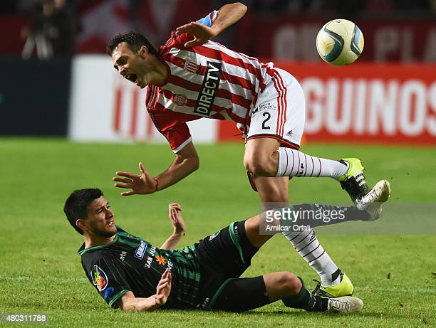 Leandro Desabato of Estudiantes de la Plata loses the ball against the slide of Facundo Pumpido of San Martin during a match between Estudiantes and...