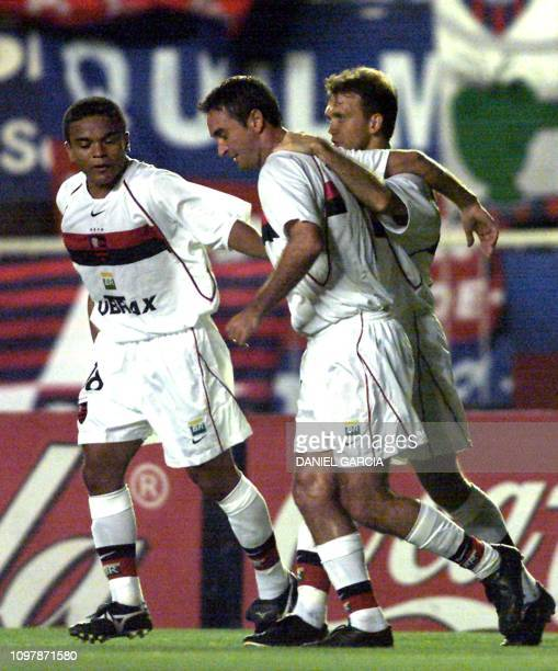 Leandro Machado of the Flamengo team is congratulated by teammates Roma adn Petkovic after scoring a goal off the San Lorenzo team 24 January 2002 in...