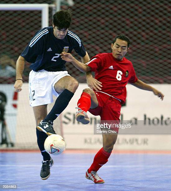 Leandro Miguel Planas of Argentina battles with Listiyanto Raharjo of Indonesia during the match between Argentina and Indonesia in the 2003 World...
