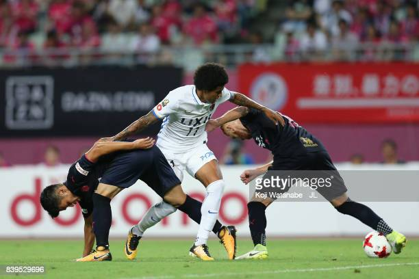 Leandro of Kashima Antlers competes for the ball against Hotaru Yamaguchi and Souza of Cerezo Osaka during the J.League J1 match between Cerezo Osaka...