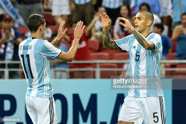 Leandro Paredes of Argentina celebrates with Angel Di Maria after scoring a goal against Singapore during their international friendly football match...