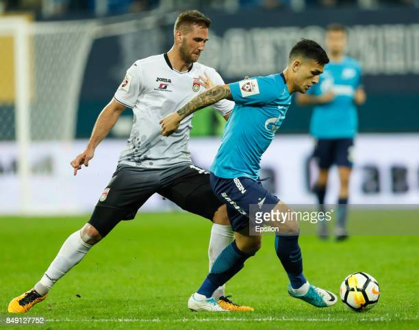 Leandro Paredes of FC Zenit Saint Petersburg and Ivan Paurevic of FC Ufa vie for the ball during the Russian Football League match between FC Zenit...