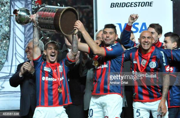 Leandro Romagnoli and Nestor Ortigoza of San Lorenzo lift the trophy after the second leg final match between San Lorenzo and Nacional as part of...