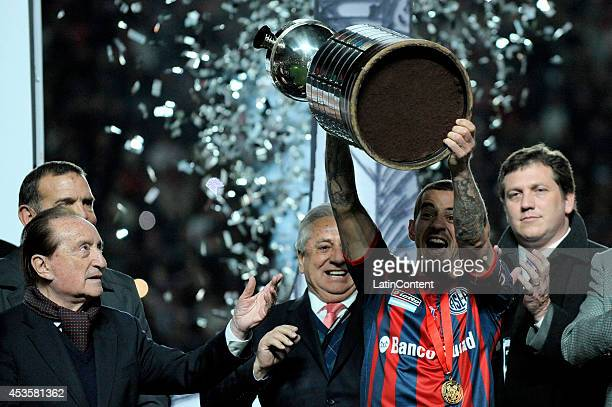 Leandro Romagnoli of San Lorenzo receives the Copa Libertadores cup after winning the second leg final match between San Lorenzo and Nacional as part...