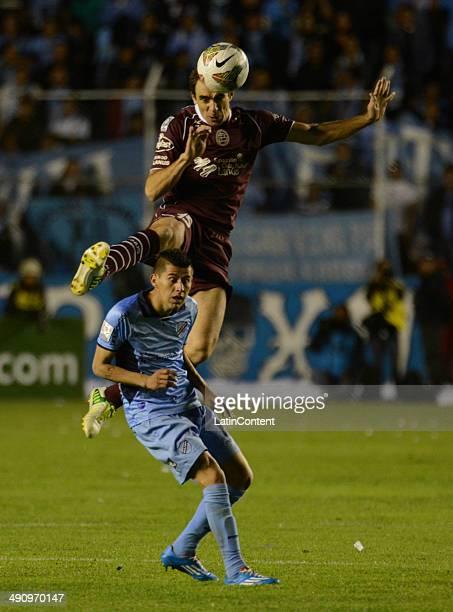 Leandro Somoza of Lanús heads the ball over Juan Carlos Arce of Bolívar during a second leg quarter final match between Bol'ívar and Lanœús as part...