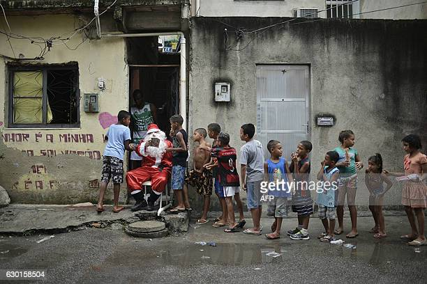 TOPSHOT Leandro Souza who lives in the favela da Mare complex one of the most violents in Rio de Janeiro dresses as Santa Claus to distribute gifts...