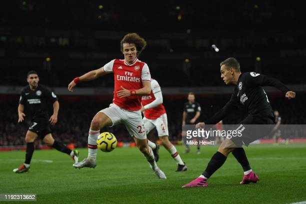 Leandro Trossard of Brighton Hove Albion crosses despite the efforts of David Luiz of Arsenal during the Premier League match between Arsenal FC and...