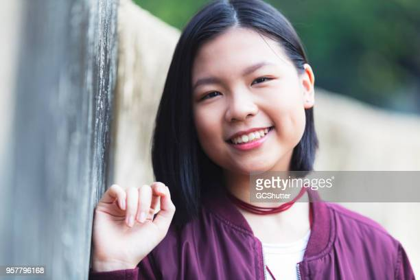 leaning happily against the wall and looking towards the camera. - malaysia beautiful girl stock photos and pictures