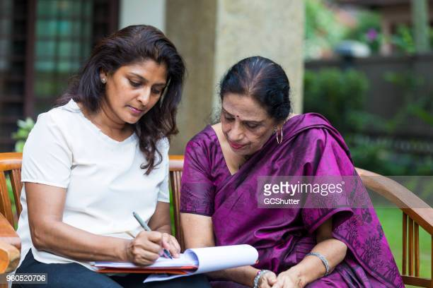 leaning into the paper as the daughter fills up the last few sections of the document. - indian culture stock pictures, royalty-free photos & images