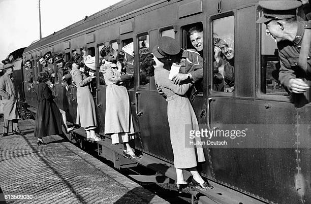 Leaning out of train windows at Feltham Station soldiers departing for Egypt kiss their wives and girlfriends goodbye September 1935
