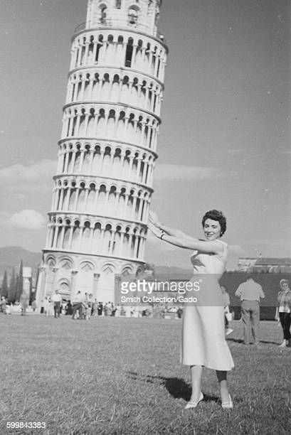 Leaning Tower of Pisa a young female tourist in a dress standing in a field smiling and pretending to hold up the tower other tourist groups standing...
