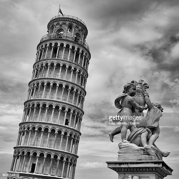 Leaning Tower Of Pisa And Statue Against Cloudy Sky