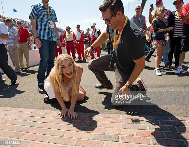 LeAnn Rimes and her husband Eddie Cibrian react after the couple kissed the bricks during the 2014 Indy 500 at Indianapolis Motor Speedway on May 25...