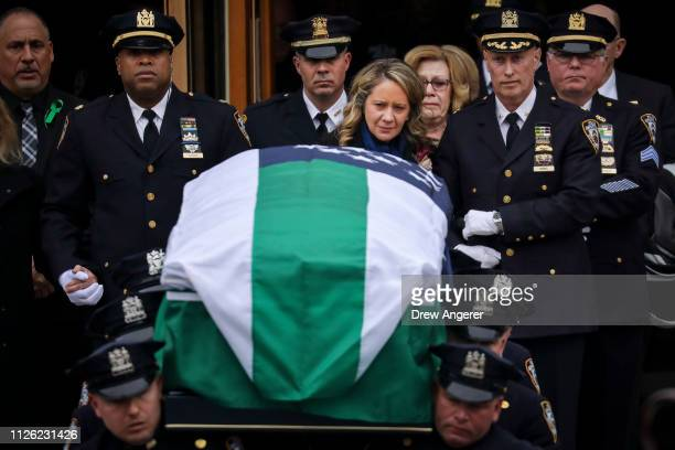 Leanne Simonsen wife of fallen NYPD Detective Brian Simonsen is escorted by officers as her late husband's remains are carried out of the church...