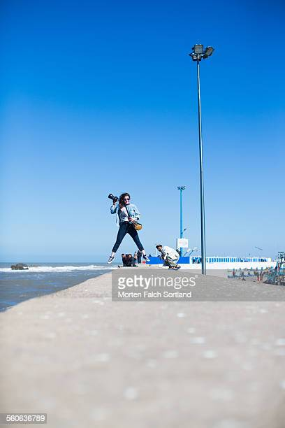 leaping on the seawall - seawall stock pictures, royalty-free photos & images