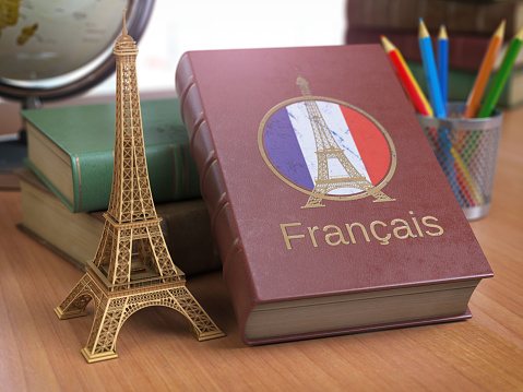 Learn and studiyng French concept. Book with  French flag and Eiffel tower on the table. 1000152558