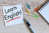 Learn english - note at wooden background with teachers glasses