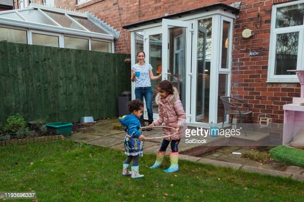 learning how to hula hoop - green coat stock pictures, royalty-free photos & images