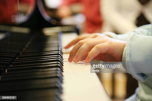 Learning music at the conservatory piano lesson Child's hand playing the piano Child music keyboard and struck string instruments