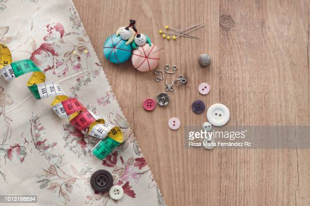 Learning objects. Fabric with sewing item and accesories which are required to learn to sew on wooden table background. Directly above and copy space.