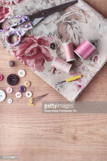 learning objects. fabric with sewing item and accesories which are required to learn to sew on wooden table background. directly above and copy space. - button sewing item stock pictures, royalty-free photos & images