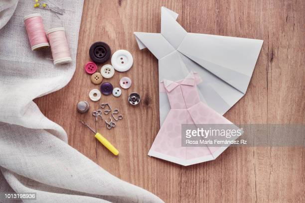 Learning objects. Fabric with sewing item which are required to learn to sew and two origami dresses on wooden table background. Directly above and copy space.
