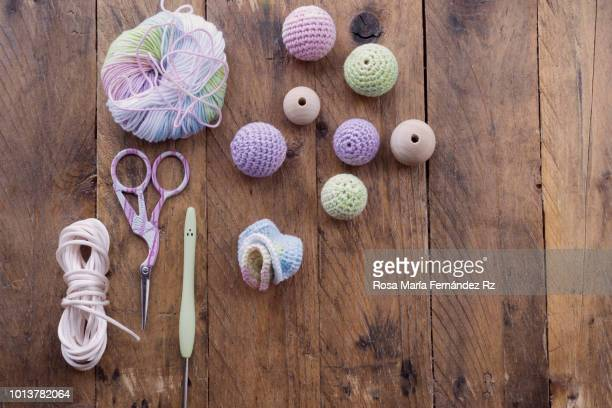 Learning objects. Item for beginner crochet starded. Multi colored wool ball, crochet needles, scissors and Knitted amigurumi balls on rustic wooden table. Directly above and copy space