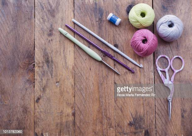 Learning objects. Item for beginner crochet starded. Multi colored yarn balls, crochet needles and scissors on rustic wooden table. Directly above and copy space