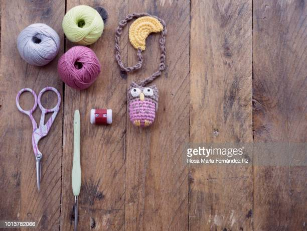 Learning objects. Item for beginner crochet starded. Multi colored yarn balls, crochet needles, scissors and knitted amigurumi little owl made of crochet on rustic wooden table. Directly above and copy space