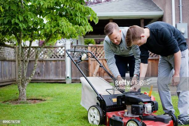 learning to cut the grass - lawn mower stock pictures, royalty-free photos & images