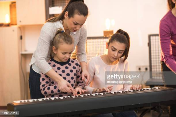 learning to play musical instrument in a group - electric piano stock photos and pictures