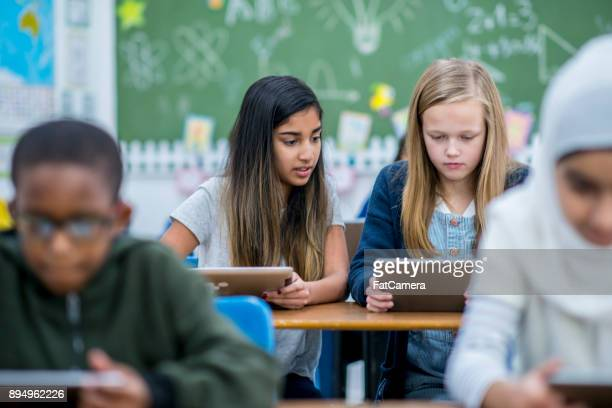 learning to use tablets - migrant children stock photos and pictures