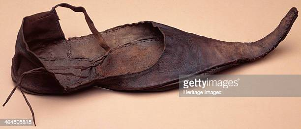 Leather adult's shoe, medieval. This pointed shoe has straps which were probably fastened around the wearer's ankle.