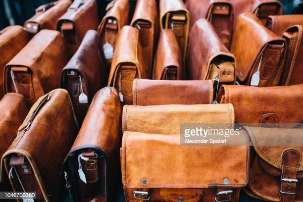 leather bags at the market stall at portobello road market in london, england - business finance and industry stock pictures, royalty-free photos & images