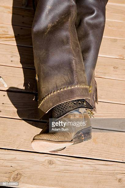 leather boots and chaps of a cowboy lying on a wooden floor - bottes en cuir photos et images de collection