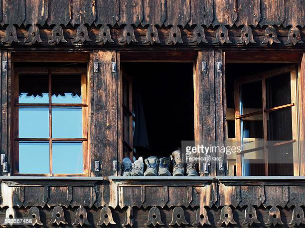 Leather Boots On A Wooden Window Of Traditional Chalet In The Swiss Alps
