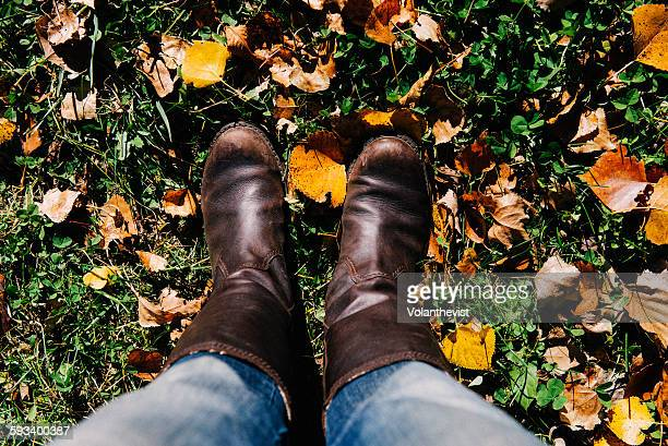 Leather boots on the grass with autumn leaves