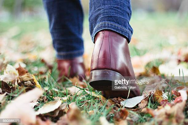 Leather boots walking over fallen autumn leaves