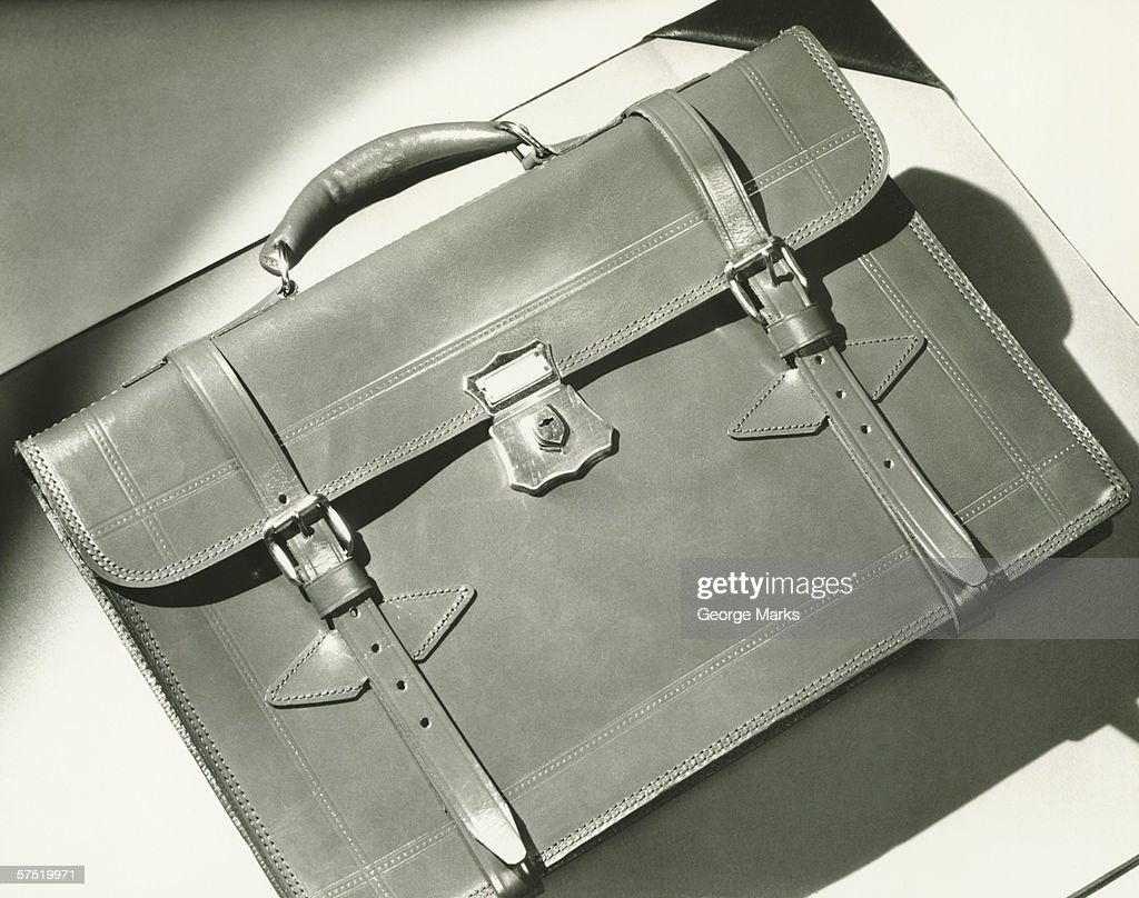 Leather briefcase lying on white blotter, (B&W), close-up : Stock Photo
