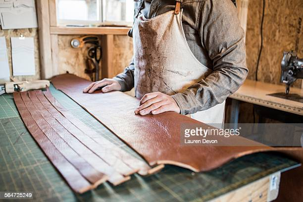 Leather craftsman with strips of leather on workshop bench