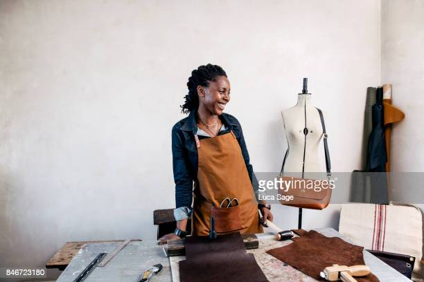 A leather craftswoman laughing behind her work bench
