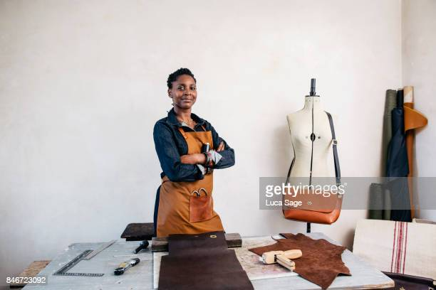 a leather craftswoman stands behind her desk, smiling to camera - leather stock pictures, royalty-free photos & images