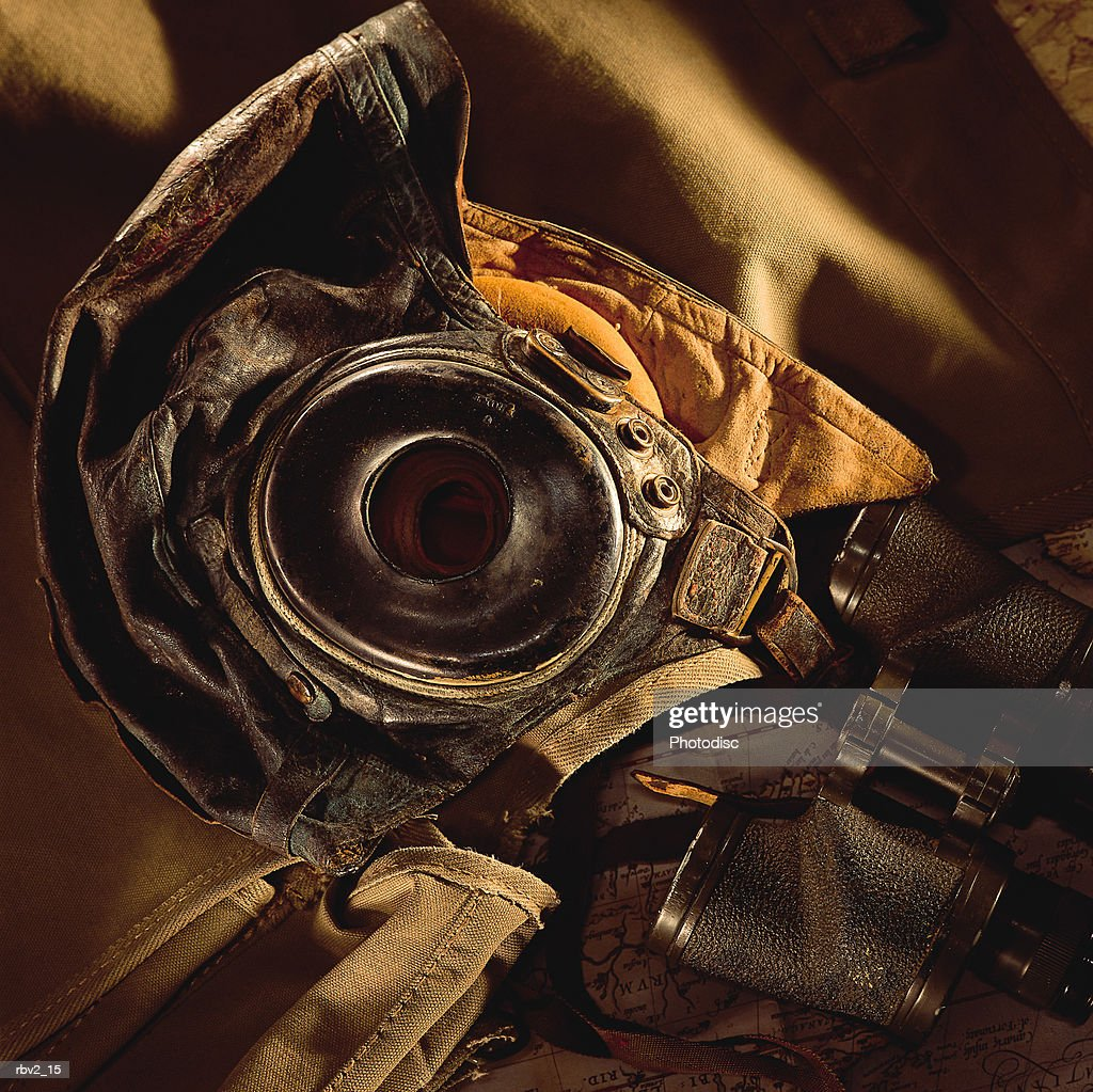 leather gloves and a helmet and binoculars lie together on a brown background : Foto de stock