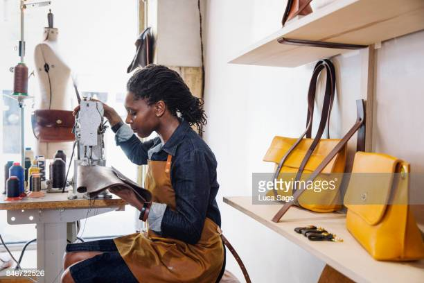leather handbag store with designer working at her sewing machine - leather purse stock pictures, royalty-free photos & images