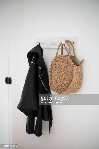 leather jacket with wicker bag hanging on hooks at home - jacke stock-fotos und bilder