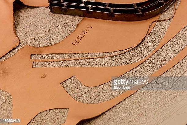 Leather shapes cut out of a piece of cow hide sit on a cutting table before attaching to chair covers at the Fritz Hansen A/S furniture company's...