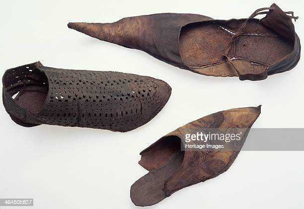 Leather shoes, medieval. One of the shoes is pierced and it is not as pointed as the others. The one that looks like a flip-flop has a leaf-design on...