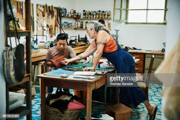 leather shop owner assisting employee with design of purse in workshop - schuhmacher stock-fotos und bilder