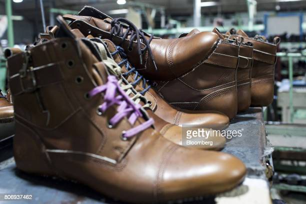 Leather uppers fitted with lasts sit on top of a heat treatment machine on the production line at a Virola Shoes Pvt manufacturing facility in Agra...